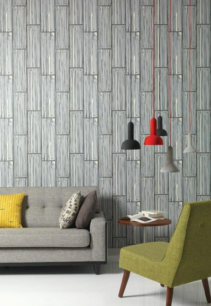 une idée pour habiller un mur en papier peint aux motifs poutres de bois cloués au mur, motifs amusants humoristiques, ambiance arty, fauteuil en tissu vert, canapé gris avec des coussins carrés en gris et en noir et blanc, carrelage blanc