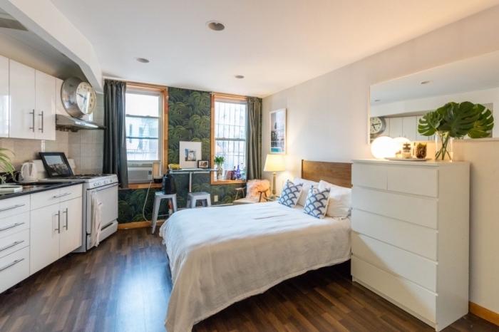 choisir un revêtement de murs tendance, déco de studio avec grand lit et petite cuisine aux armoires blanches