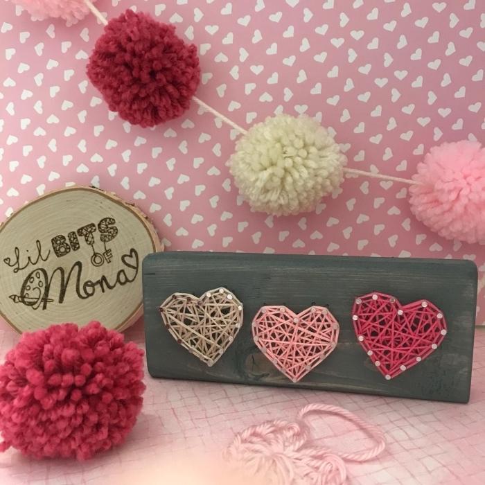 exemple d'accessoires et objets décoratifs dans un coin rose pastel décoré avec guirlande de pompons en laine