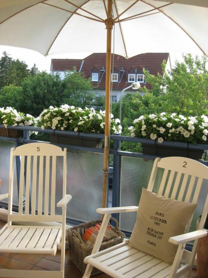 deux chaises pliantes en plastique couleur ivoire avec des numéros sur leurs dossiers, decoration jardin terrasse, parasol tissu blanc et bois clair