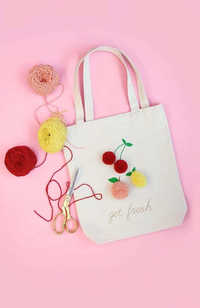modèle de sac pour faire les courses de couleur beige avec ornement en formes de fruits de pompons de laine