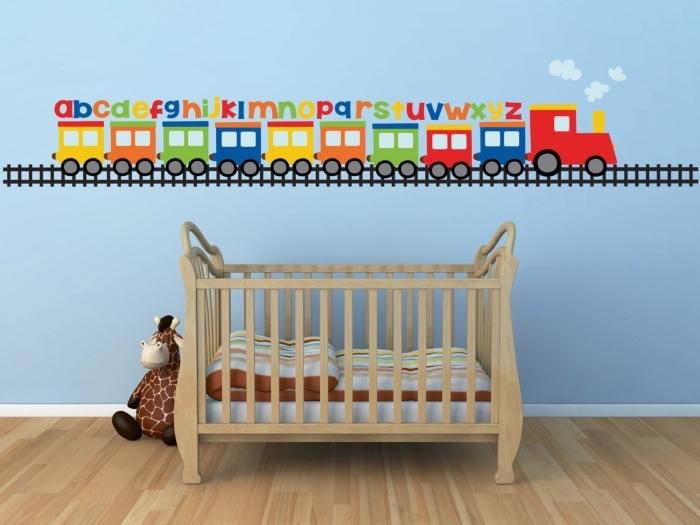 idée pour la déco murale dans une pièce nouveau-né aux murs bleus avec dessin à design train multucolore