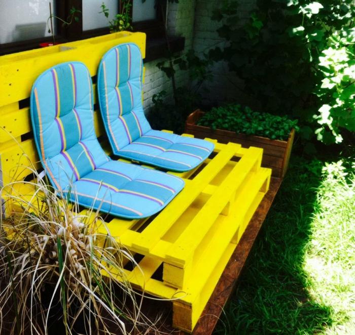 banquette en palette peinte en jaune flashy et recouverte de deux matelas en bleu pastel et en jaune, meubles de jardin en palettes posés a l'ombre d'un arbre