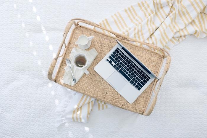 surprendre une femme avec un petit déjeuner au lit servit sur un plateau beige avec tasse de thé et son notebook