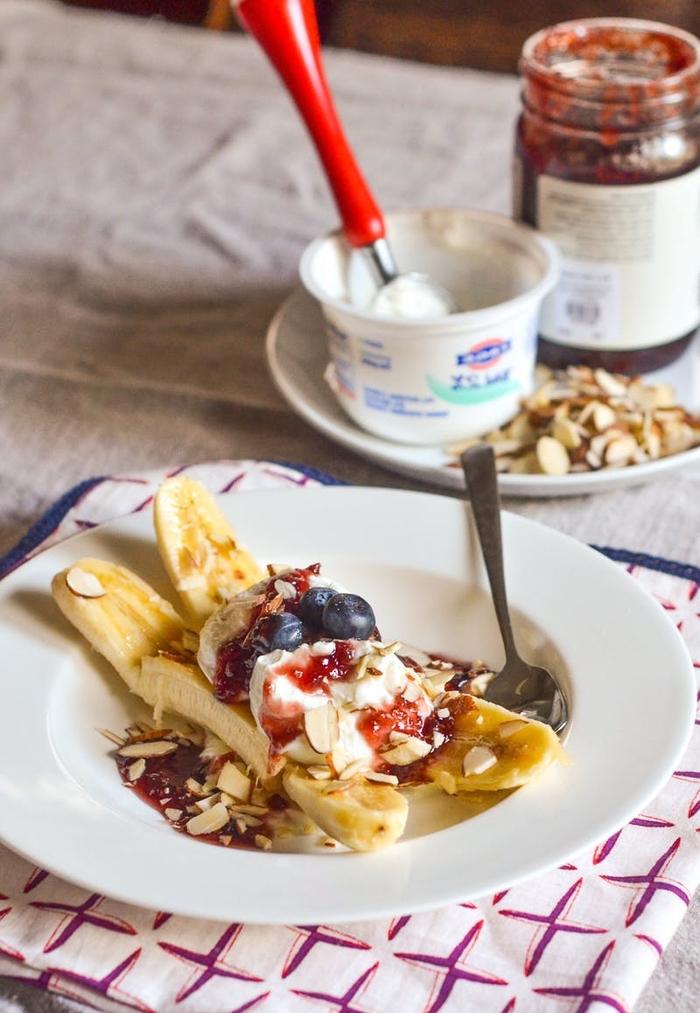 des moitiés de banane au yaourt nature, myrtilles et amandes effilées pour un petit déjeuner diététique et léger