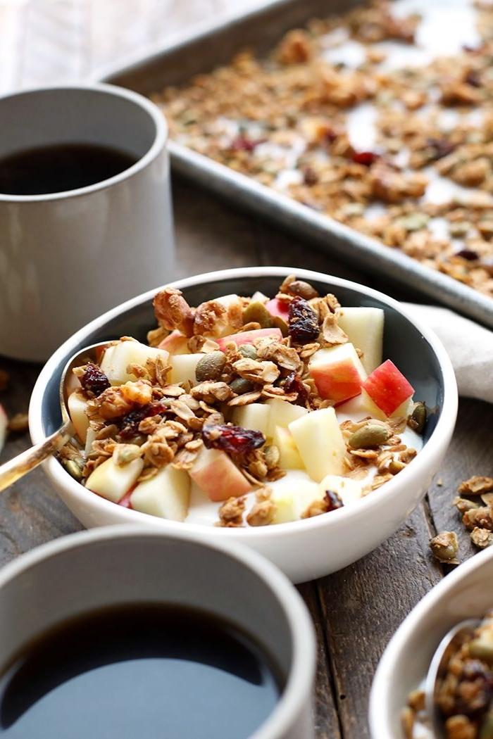 bowl de petit-déjeuner sain de muesli, yaourt grec, pommes, fruits séchés et graines