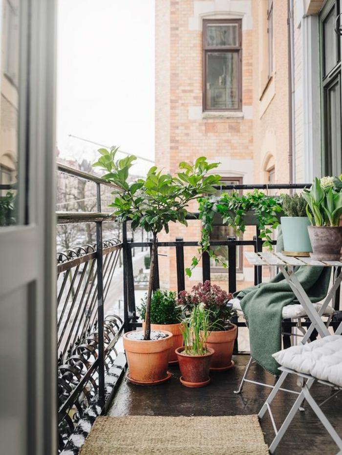 petite terrasse parisienne, idee amenagement terrasse, six pots avec des plantes vertes, sol recouvert de dalles en noir lisses, tapis en paille, chaises et table pliable en métal gris