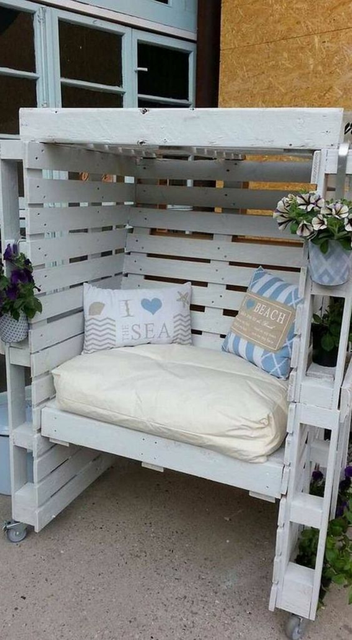 petite construction en palettes en bois blanc, canapé palette couvert avec un toit dessus, meuble recouvert de matelas en couleur ivoire et deux coussins carrés en blanc et bleu pastel