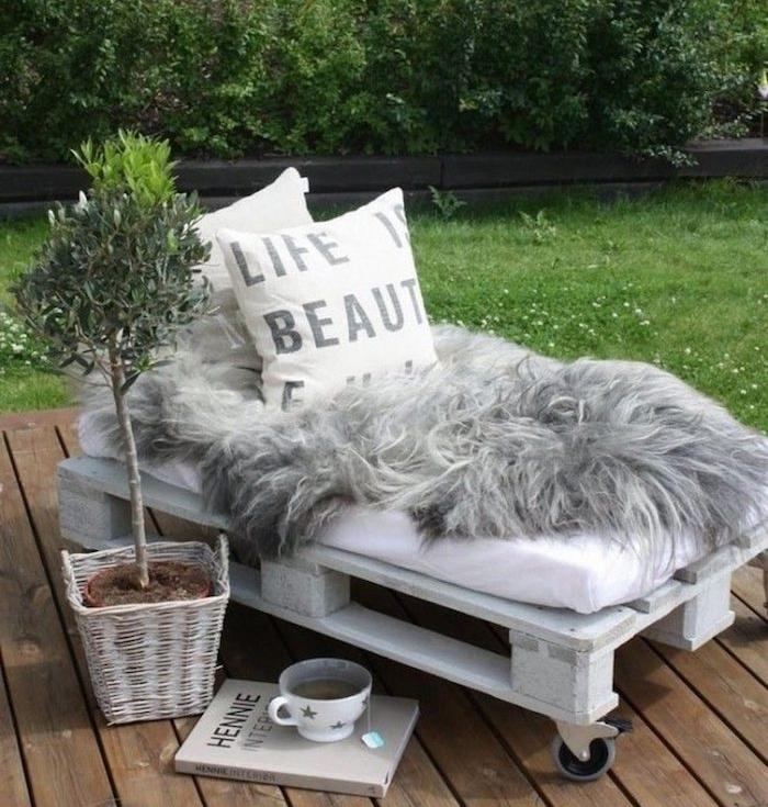 petite assise en palette à roulettes style cocooning avec des coussins décoratifs et coussin d assise blanc, plante verte, gazon
