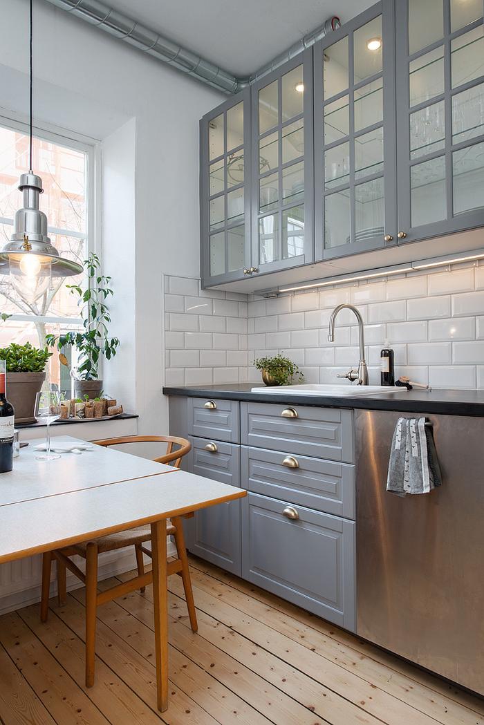 petite cuisine grise et blanche de style scandinave avec crédence de fausses briques blanches, des meubles hauts avec portes vitrées et un parquet en bois clair