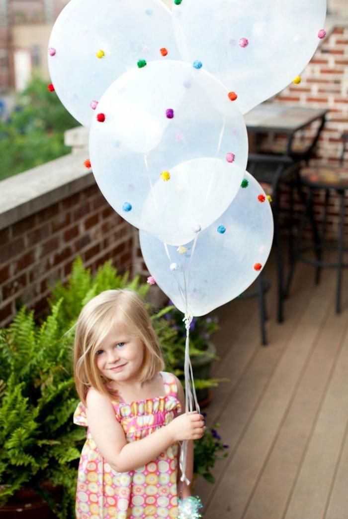idée pour la décoration festive, comment organiser un anniversaire d'enfant, déco avec ballons transparents décorés de pompons