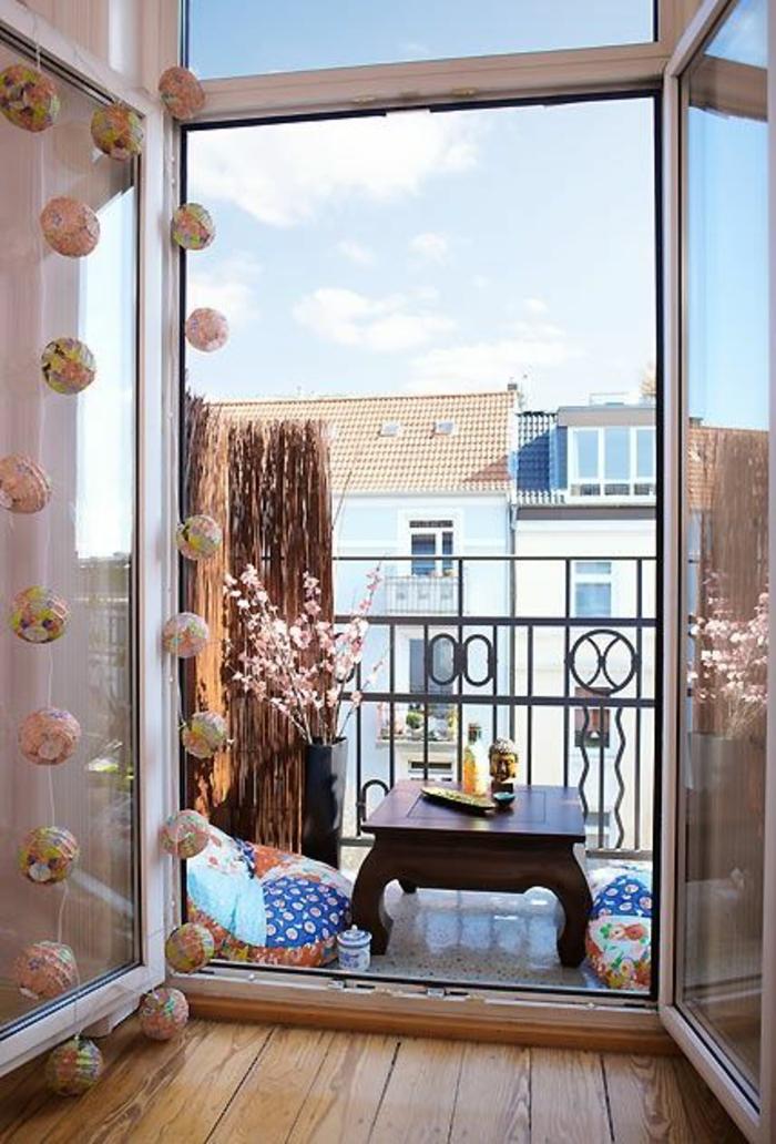 ambiance zen, terrasse en style asiatique, idee amenagement terrasse, table bases en bois marron avec tete de Bouddha, garde-corps en métal noir avec des figures ovales et rondes