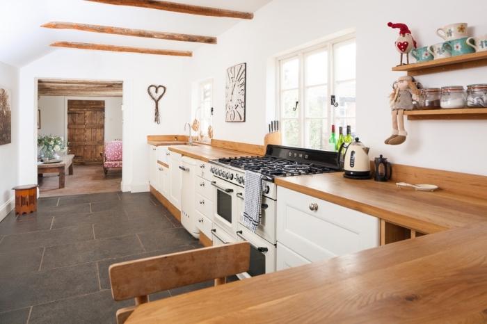 aménagement de cuisine rustique aux murs blancs avec armoires blanches et comptoir de bois stratifié marron