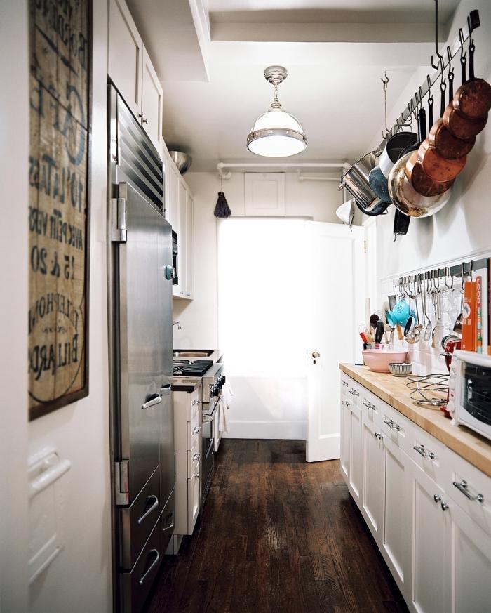 astuces rangement dans une petite cuisine aménagée en deux rangées avec meubles blancs à plan de travail bois clair
