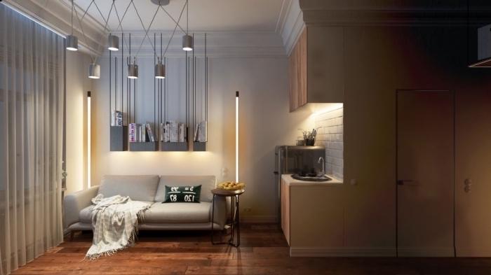 ambiance cozy dans un petit studio aménagé avec meubles multifonctions, canapé escamotable et éclairage à finition métallique