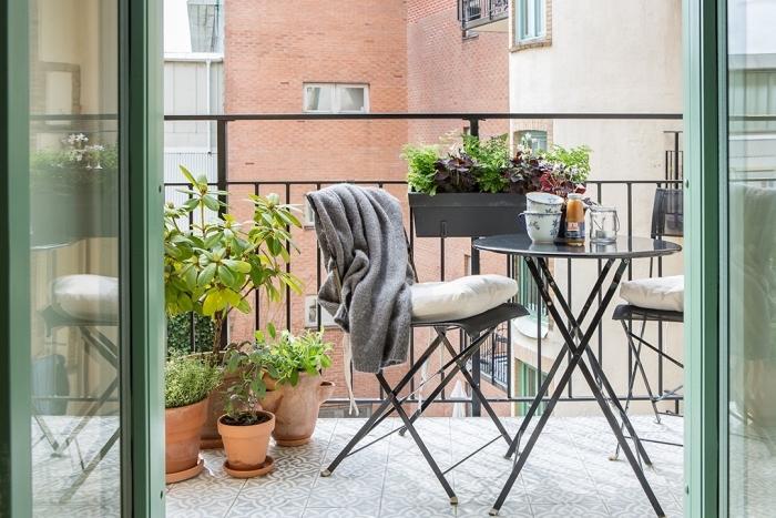 aménagement de balcon avec table ronde et chaises noires, déco de mini jardin urbain avec plantes comestibles