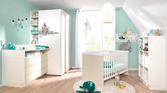 murs vert pastel et plafond blanc dans une pièce au plancher stratifié aménagée avec meubles en bois blanc