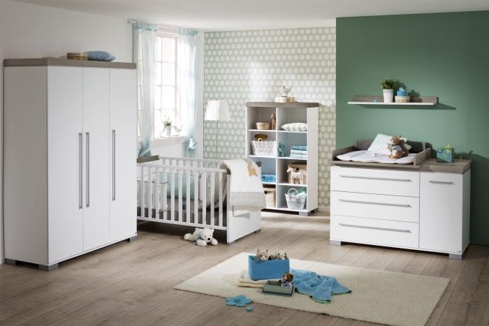 modèle de chambre bébé neutre avec pan de mur vert et papier peint à design géométrique en blanc et vert pâle