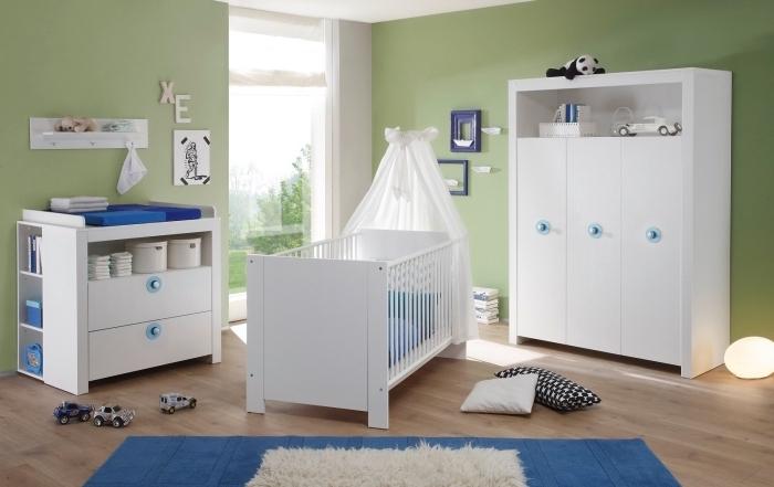 modèle d'intérieur moderne dans une pièce nouveau-né aux murs vert clair et plancher de bois stratifié aménagée avec mobilier blanc