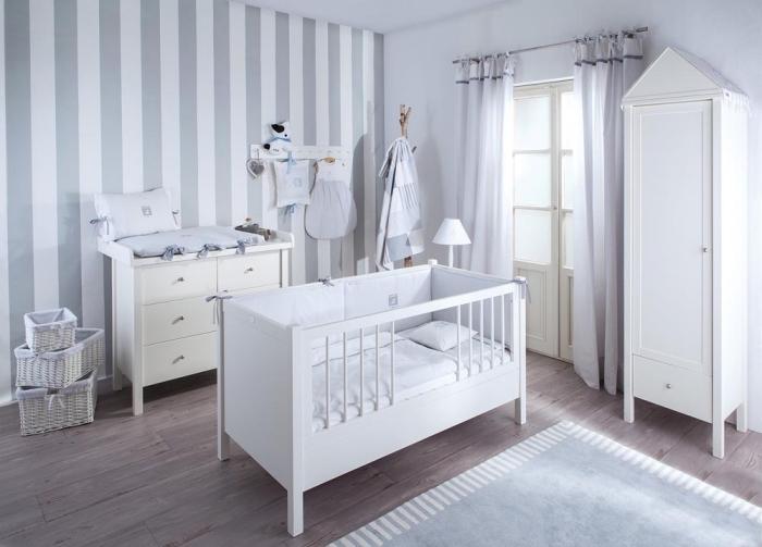 chambre nouveau-né aux murs blancs avec pan de mur en papier peint rayé blanc et gris clair, mobilier de bois blanc