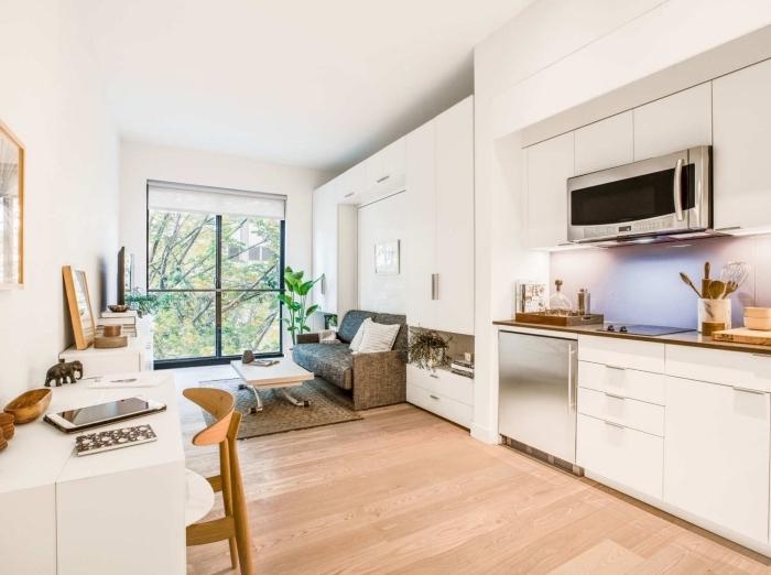 modèle de studio aux design minimaliste avec murs blancs et meubles de bois multifonctions, déco de cuisine en blanc et argent
