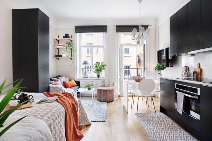 idée déco studio en meubles blanc et noir, ambiance cozy avec un pouf multicolore et coussins et plaid orange