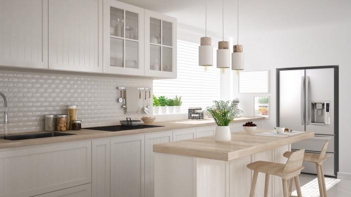 idée déco minimaliste dans une cuisine moderne équipée d'un ilot central en bois clair avec chaise de bar en bois