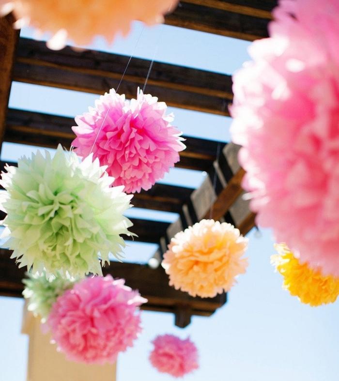 idée décoration extérieur pour une fête ou anniversaire, pompon papier de soie de couleurs et tailles variées pour une déco festive