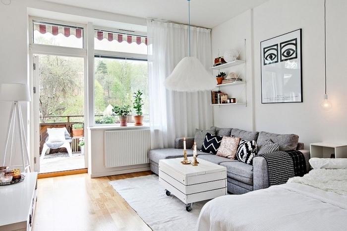 déco cozy dans un petit studio étudiant ou célibataire avec canapé et grand lit, aménagement de balcon avec plantes vertes et chaise cocooning