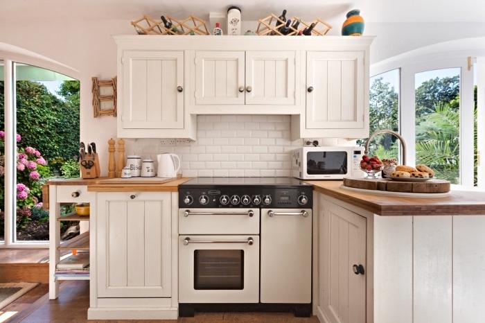 déco de style campagnarde dans une petite cuisine aménagée avec meubles blancs et comptoir de bois massif