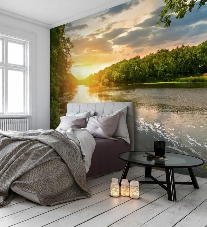 poster géant dans la chambre à coucher, lit gris, table basse noire, plancher en bois blanc