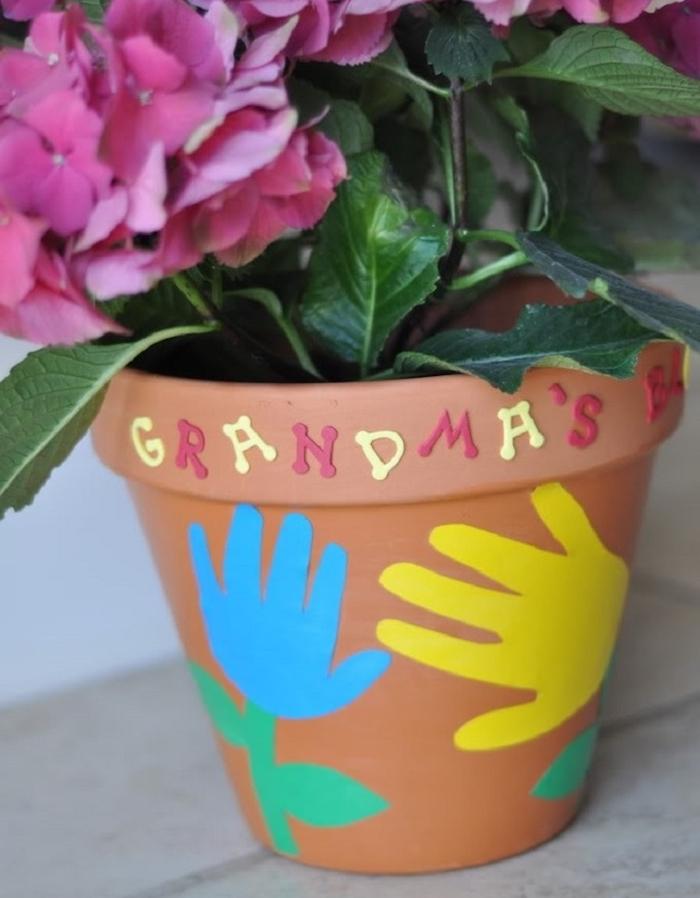 pot de fleur en terre cuite avec des empreintes de main et fleur originale, diy fete des meres facile