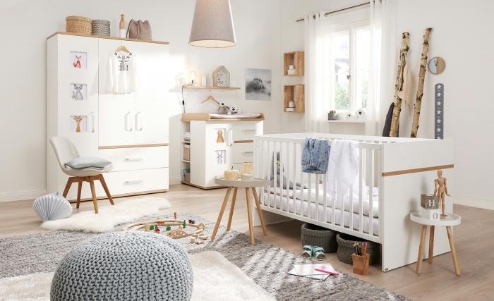 modèle de chambre bebe complete en blanc et bois avec large tapis large moelleux et pouf en crochet de nuance grise