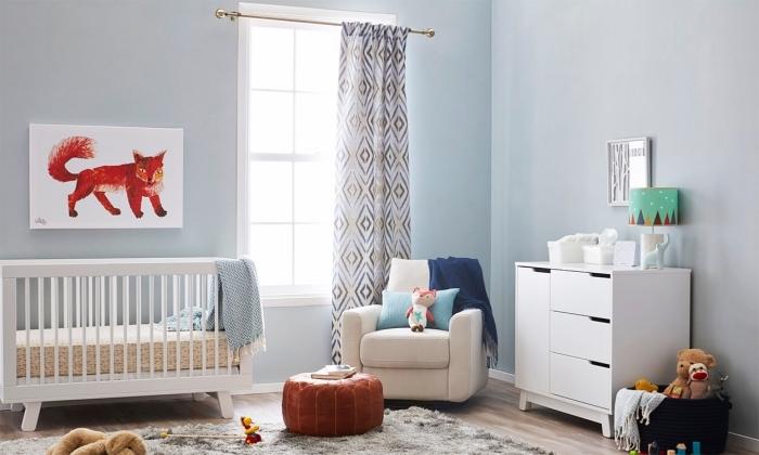 déco mignonne dans une pièce aux murs bleu pastel avec meubles de bois blanc et plancher stratifié couvert de tapis moelleux gris