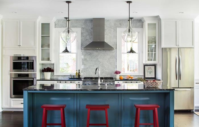 cuisine blanche et grise où le carrelage de la crédence effet marbre se prolonge jusqu'au plafond, cuisine gris et blanc dynamisée par son îlot central rouge et bleu