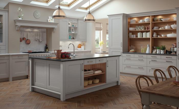 une cuisine gris clair de style campagne chic équipée d'un îlot central et des meubles avec niches bois