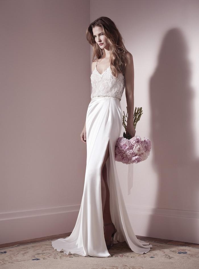 robe de mariée originale avec une jupe blanche moulante et un corsage en dentelle, bouquet de mariée rose