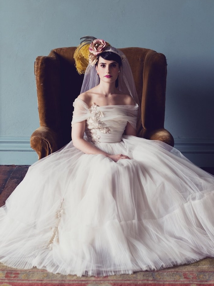 modèle de robe de mariée princesse retro chic avec une jupe en tulle blanche féerique et un top blanc plissé à épaules nues, voile et fleurs dans les cheveux