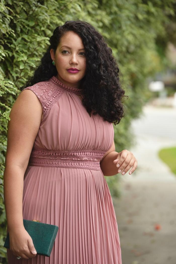 robe rose plissée, femme ronde habillée avec style, cheveux frisés, rouge à lèvres mat foncé