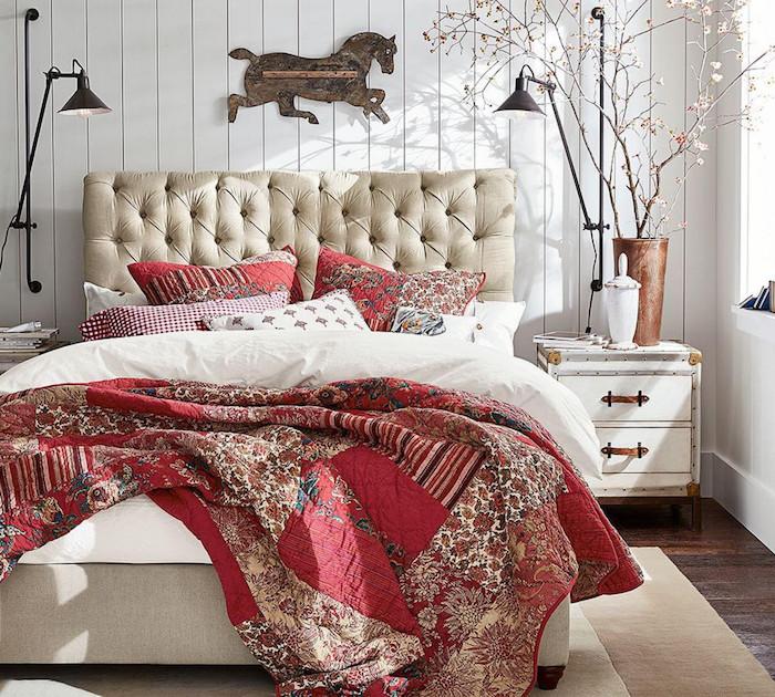 cheval en bois pour décorer une tete de lit capitonnée, linge de lit rouge et blanc, table de nuit vintage, murs en lambris blanc