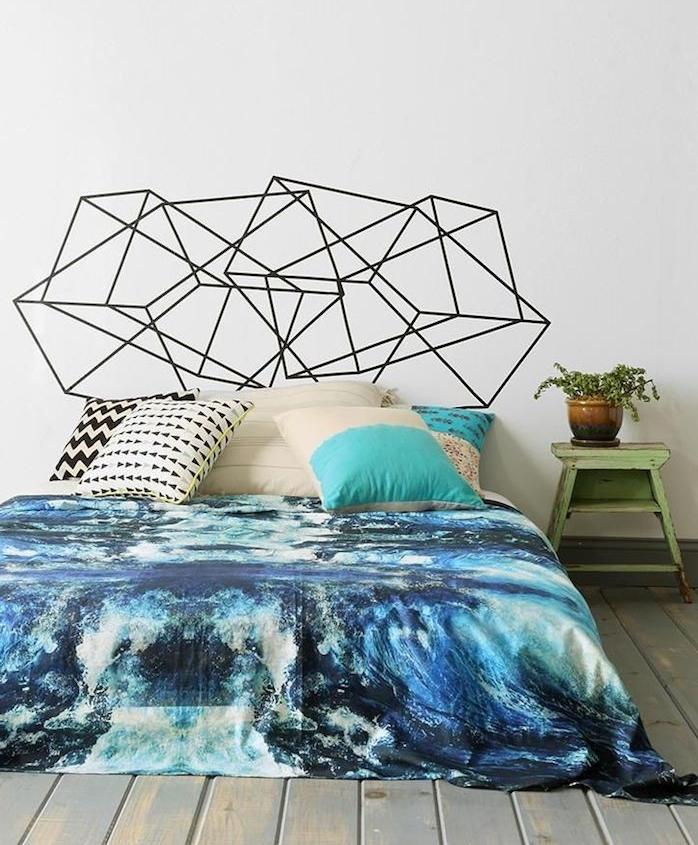 tete de lit originale en motifs geometriques noirs, linge de lit bleu, coussins décoratifs, parquet gris usé, table de nuit vintage