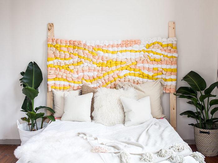 tete de lit originale en tissu mailles, linge de lit beige et blanc, plantes vertes encadrant un lit cocooning