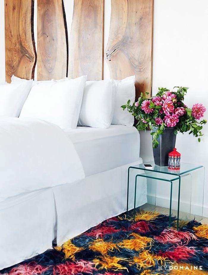 comment fabriquer tete de lit en planches de bois, linge de lit blanc, tapis coloré et bouquet de fleurs dans un vase