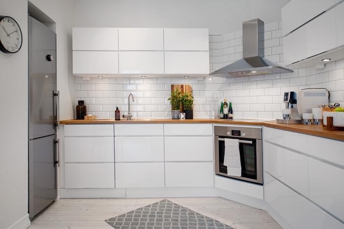 design intérieur contemporain dans une cuisine blanche au plancher de bois clair et crédence blanche à carrelage briques