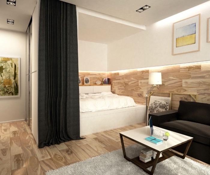 exemple comment séparer la chambre à coucher dans un studio avec rail de rideaux, intérieur moderne aux murs blancs et revêtement partiel en bois