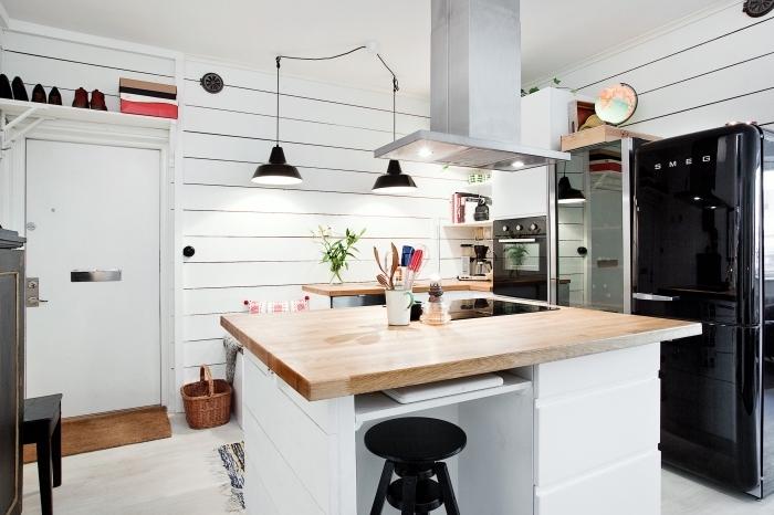esprit industriel dans un intérieur moderne aux murs blancs avec meubles de bois clair et touches noires en forme d'objets décoratifs