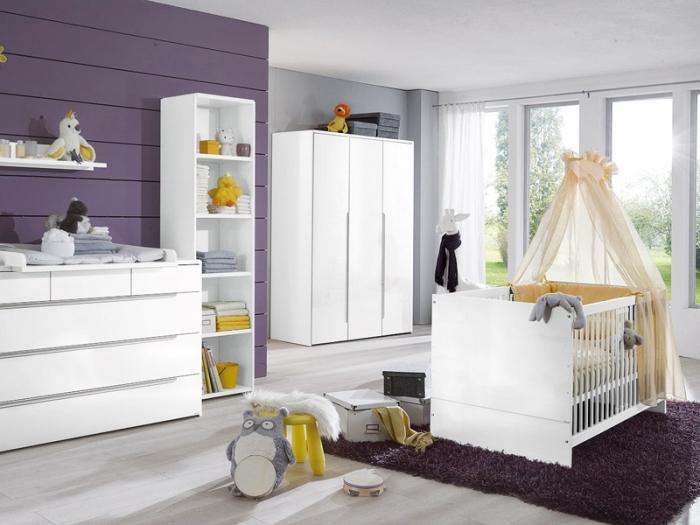 exemple de déco stylée dans une pièce cocooning pour bébé aux murs blancs et violets avec meubles blancs