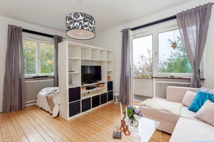 meuble rangement e bois blanc utilisé comme une bibliothèque et séparation pour diviser l'espace dans un studio