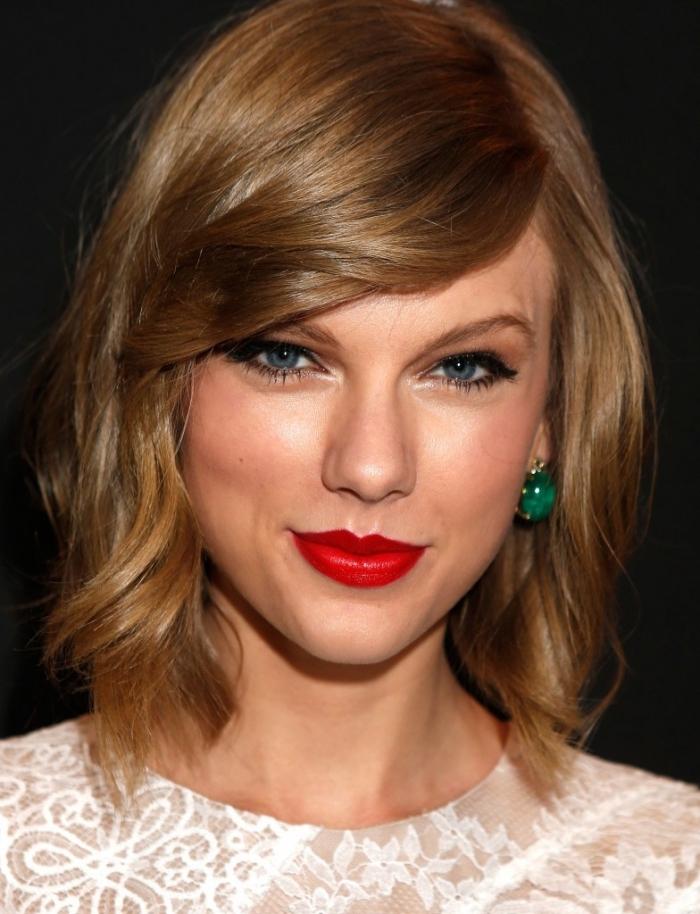 coiffure de Taylor Swift aux cheveux mi-longs avec frange de côté, couleur de cheveux châtain cuivré en carré dégradé