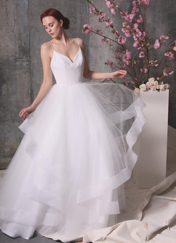 robe de mariée avec jupe en tulle plissée et un bustier blanc avec bretelles fines, chignon bas femme